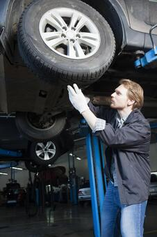 Automobile mechanic servicing tires 14