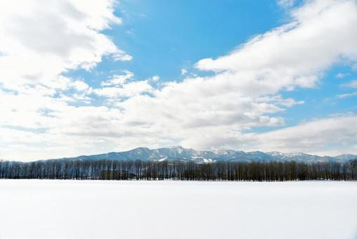 A snowy field, a mountain and a blue sky