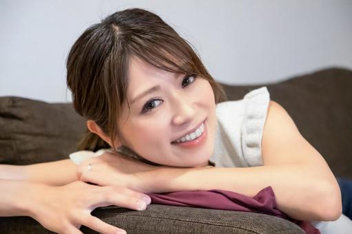 A smiling woman leaning on the sofa