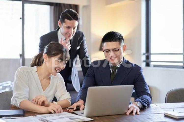 パソコンでWeb会議をするアジア人とラテン人のビジネスパーソンの写真