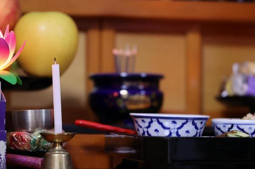 A meal of offerings and a Buddhist altar with candles