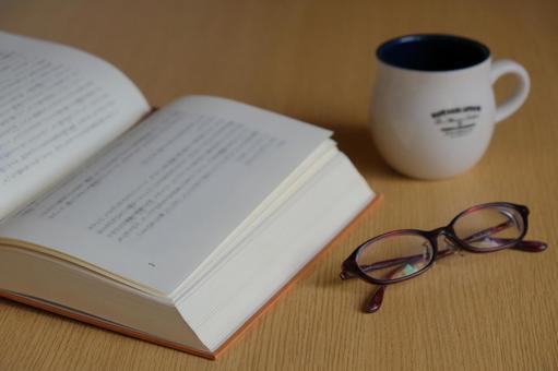 見開きの本と眼鏡とマグカップ 休憩 一息のイメージ素材