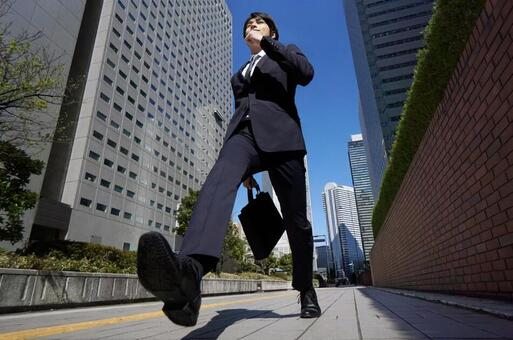 Japanese male businessman walking dashingly in the office district