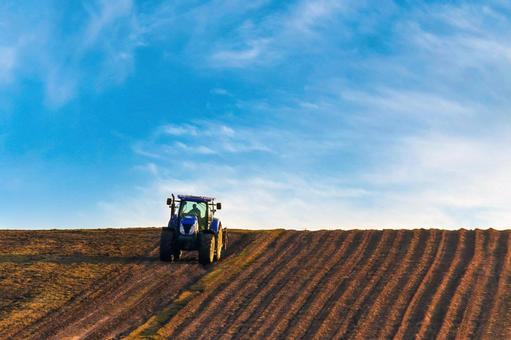 푸른 하늘과 농사중인 트랙터
