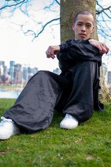 나무 아래 앉아 태극권 의상을 입은 중국인 남성