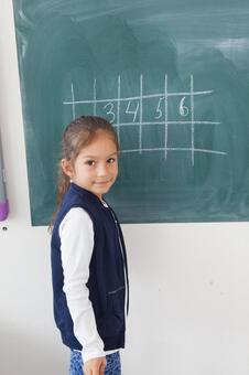小学学生在黑板上写14