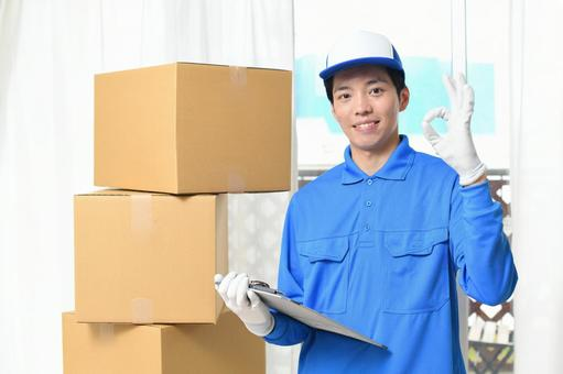 Image of a man wearing work clothes and a moving cardboard