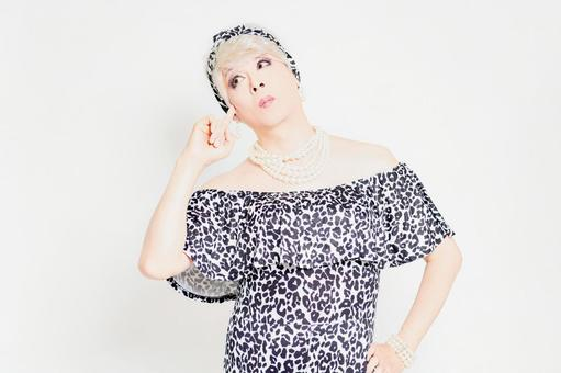 Drag queen standing in front of a white background and thinking