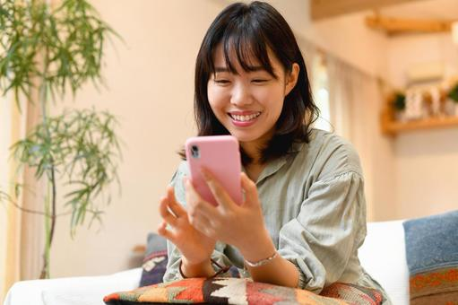 A young woman operating a smartphone indoors