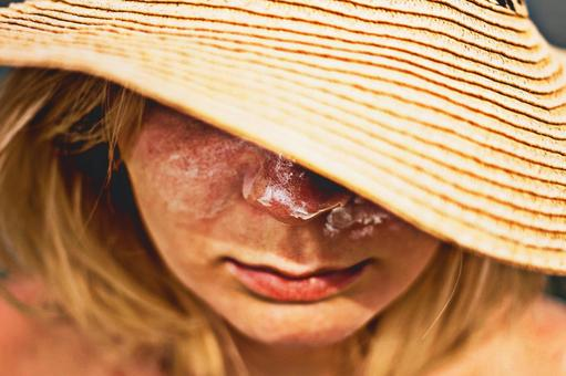 A woman hiding her face with a straw hat