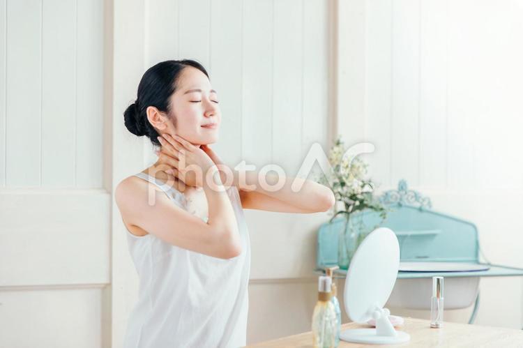 首を触る女性(笑顔)の写真