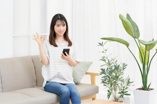 A young woman sitting on the sofa and operating a smartphone