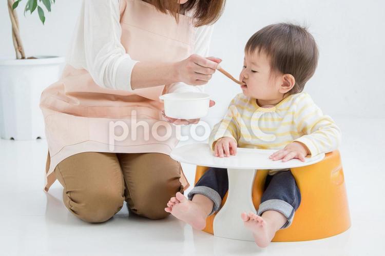 離乳食を食べさせる女性の写真