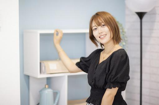 A woman touching the shelf and looking at the camera