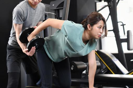 Asian women doing one-handed rowing (muscle training) and male trainers assisting