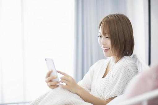 A woman looking at a smartphone with a smile