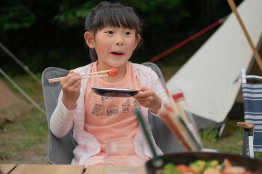 Girl eating at the camp