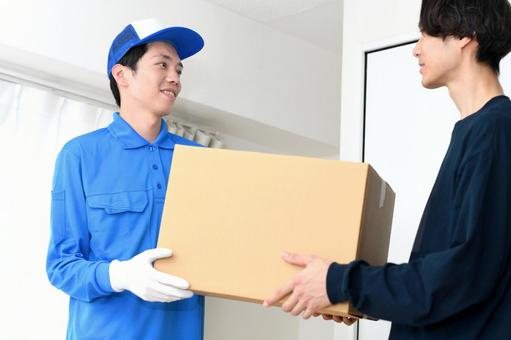 Image of a man wearing work clothes handing over luggage