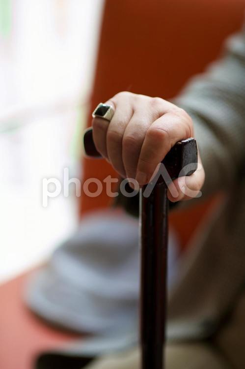 ソファーに座った男性の杖を突いている手元5の写真