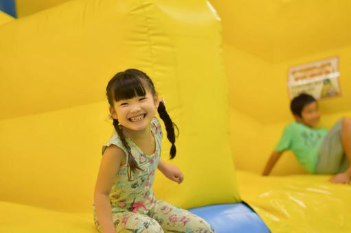 Children playing on the slide of air play equipment