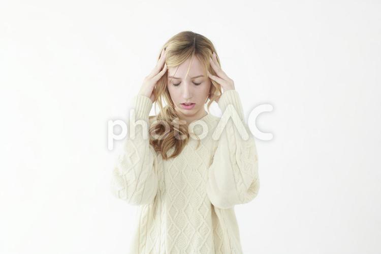 頭を押さえる女性の写真