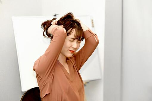 A young woman worried while grabbing her hair