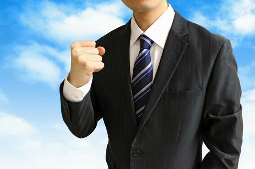 Businessman holding a fist 2 blue sky