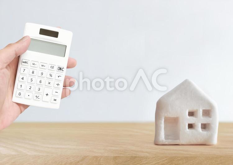 家の模型と電卓 家計 ローン 計算の写真