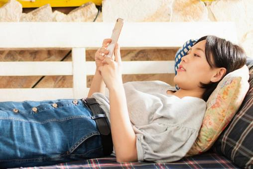 A teenage woman operating a smartphone while sleeping