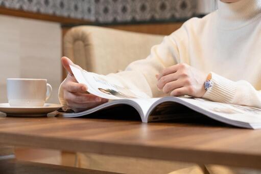 Women's hands reading fashion magazines