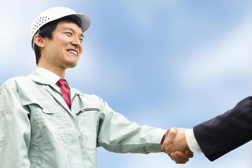 Men in work clothes shaking hands