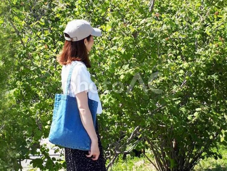 マイバッグを持って歩く女性の写真