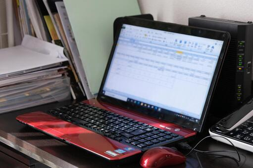 A pile of working desk documents with a laptop