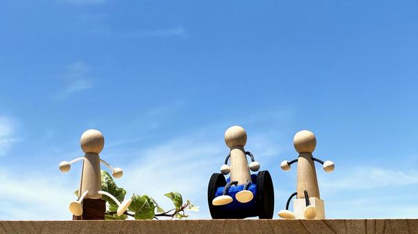 Two dolls talking with a doll in a wheelchair Image_blue sky background