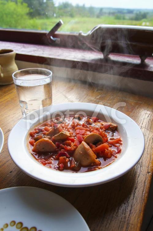 赤い野菜スープを食べるの写真