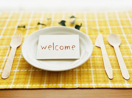 하얀 접시 위에 welcome 카드 _ 노란색 체크 점심 매트