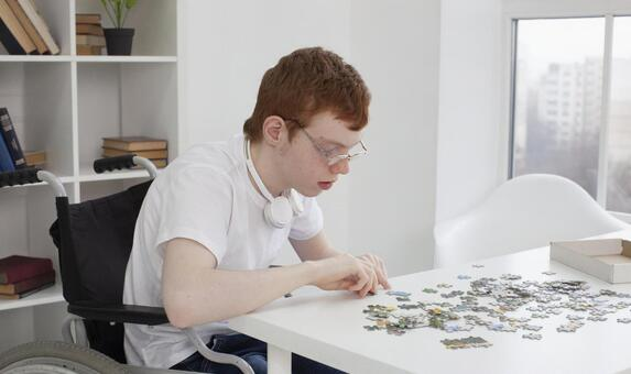 Cerebral palsy boy lining up puzzles