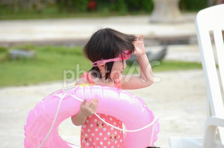 プールサイドで浮き輪を持つ女の子の写真