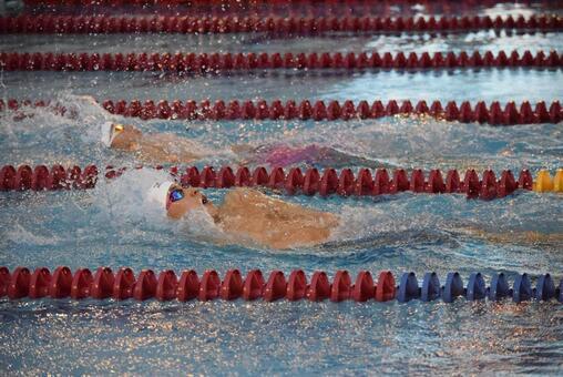 Swimmer swims backstroke