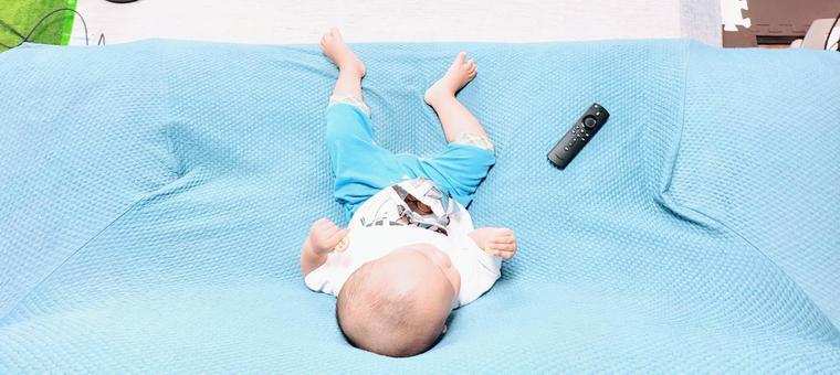 寶寶一邊看電視一邊在沙發上放鬆吃甜食