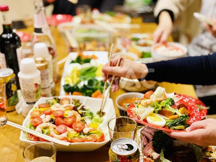 ホームパーティでサラダを取り分ける手元の写真