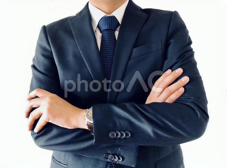 腕を組むスーツ男性の写真
