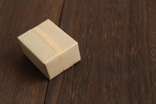 A single cardboard box placed on a wooden floor
