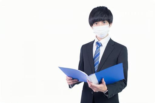 마스크를 쓰고 자료를 펼치는 젊은 일본인 사업가