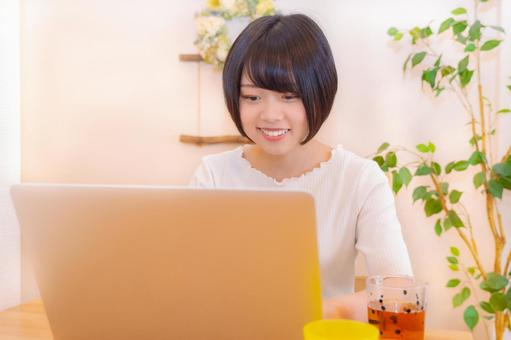 A woman looking at a computer with a smile