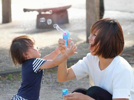 Woman and child playing with soap bubbles