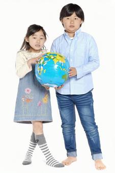 女孩和男孩1与地球沙滩球