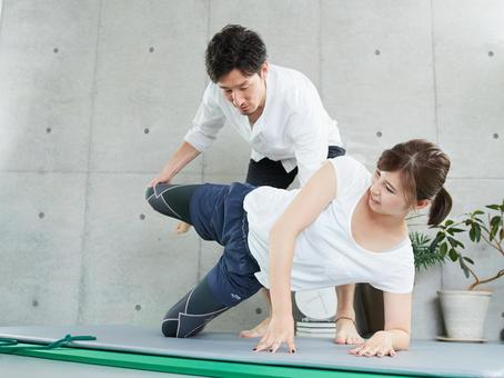 Japanese woman receiving training form instruction from a personal trainer