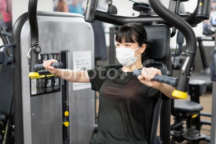 マスクしながらフィットネスジムで胸を鍛える女性の写真