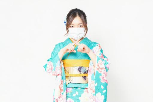 A woman wearing furisode wearing a mask and making an NG gesture